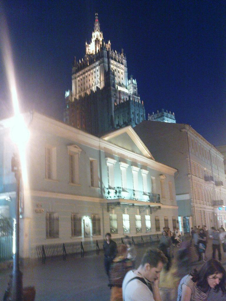 Das Puschkin-Haus auf dem Arbat am Abend, im Hintergrund der Turm des Außenministeriums